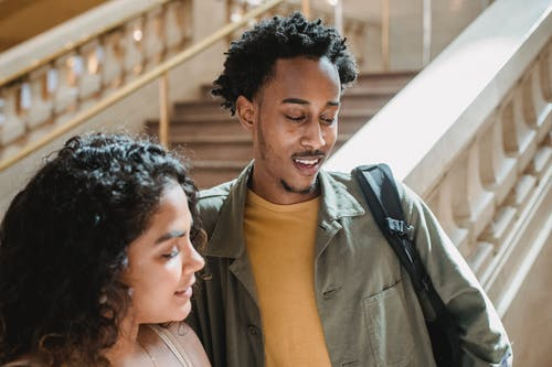 Positive young Hispanic woman and African American man in casual clothes hugging while standing near staircase in aged building