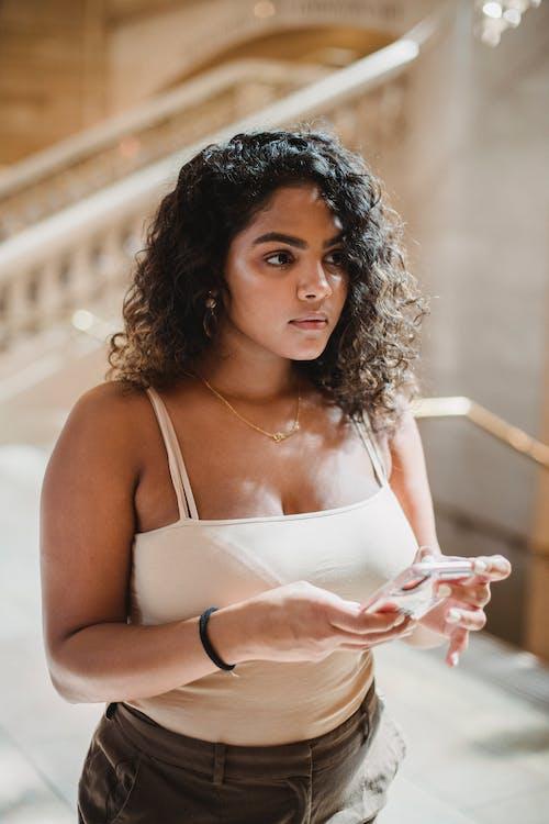 白色意大利麵條錶帶頂部拿著白色陶瓷杯的女人