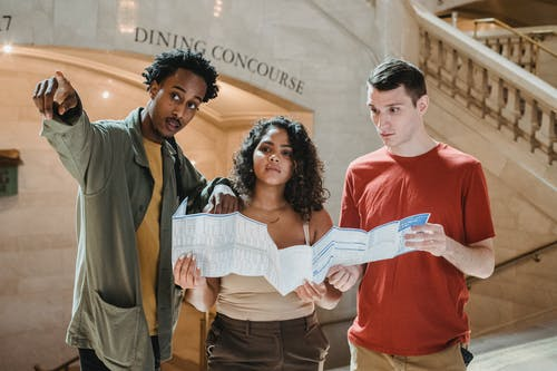 Young African American male tourist pointing away while searching for direction with diverse fiends standing in railway station terminal with paper map in hands