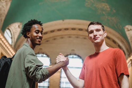 From below of positive young multiethnic male friends in casual clothes smiling and looking at camera while shaking hands in spacious aged arched building