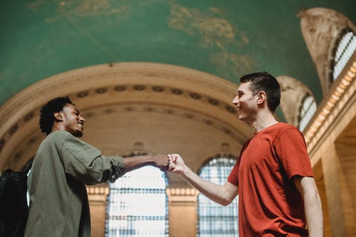 Cheerful young multiracial male friends bumping fists in old building