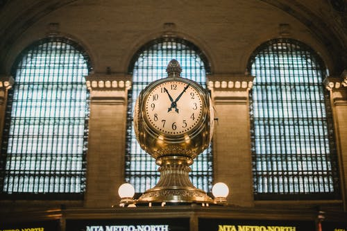 From below of aged retro golden clock placed atop information booth of historic Grand Central Terminal with arched windows