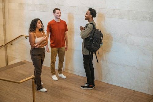 Diverse friends speaking in hallway
