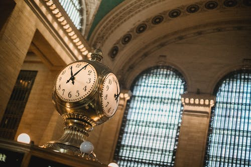 From below of vintage golden clock placed in hallway with aged interior with ornamental walls and windows and high ceilings placed in Grand Central Terminal in New Your City in daytime