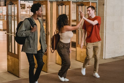 Full body of multiracial group of students looking at each other and giving high five while strolling through doorway in corridor of university building