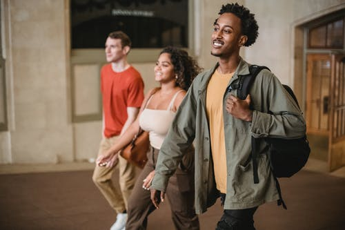 Positive African American man with male friend and Hispanic woman strolling in hallway of university building in campus on blurred background
