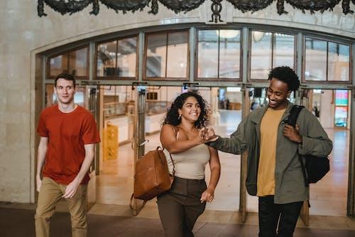 Smiling multiethnic friends walking through open doors in university