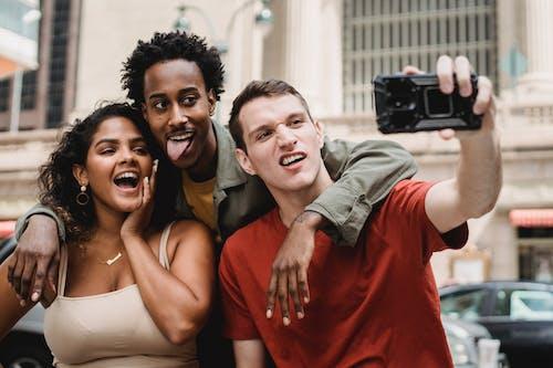 Funny multiethnic friends taking selfie on street