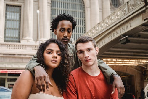 Serious multiracial group of friends hugging and looking at camera while spending time on street against historic building in city