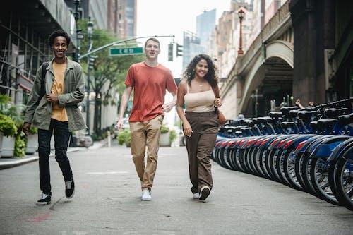 Smiling multiethnic friends walking on sidewalk