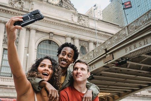 Cheerful multiethnic friends taking selfie on street