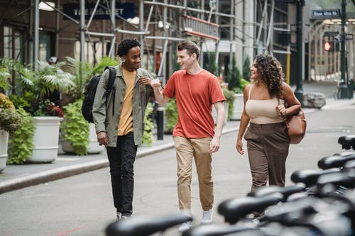 Positive multiracial men and woman strolling on walkway along metal structure and flowerpots on street with bicycles