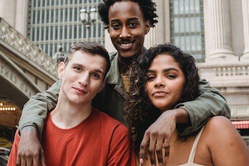 Positive black guy hugging smiling multiracial friends near urban building