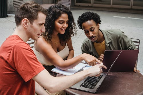 Positive multiethnic male and female students sitting together with African American friend in cafeteria and showing with finger project details on laptop