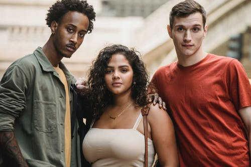 Calm diverse men and ethnic woman looking at camera while standing together