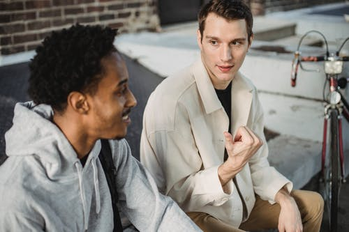 High angle of positive young multiethnic male friends in stylish clothes chilling on city street and chatting on sunny day