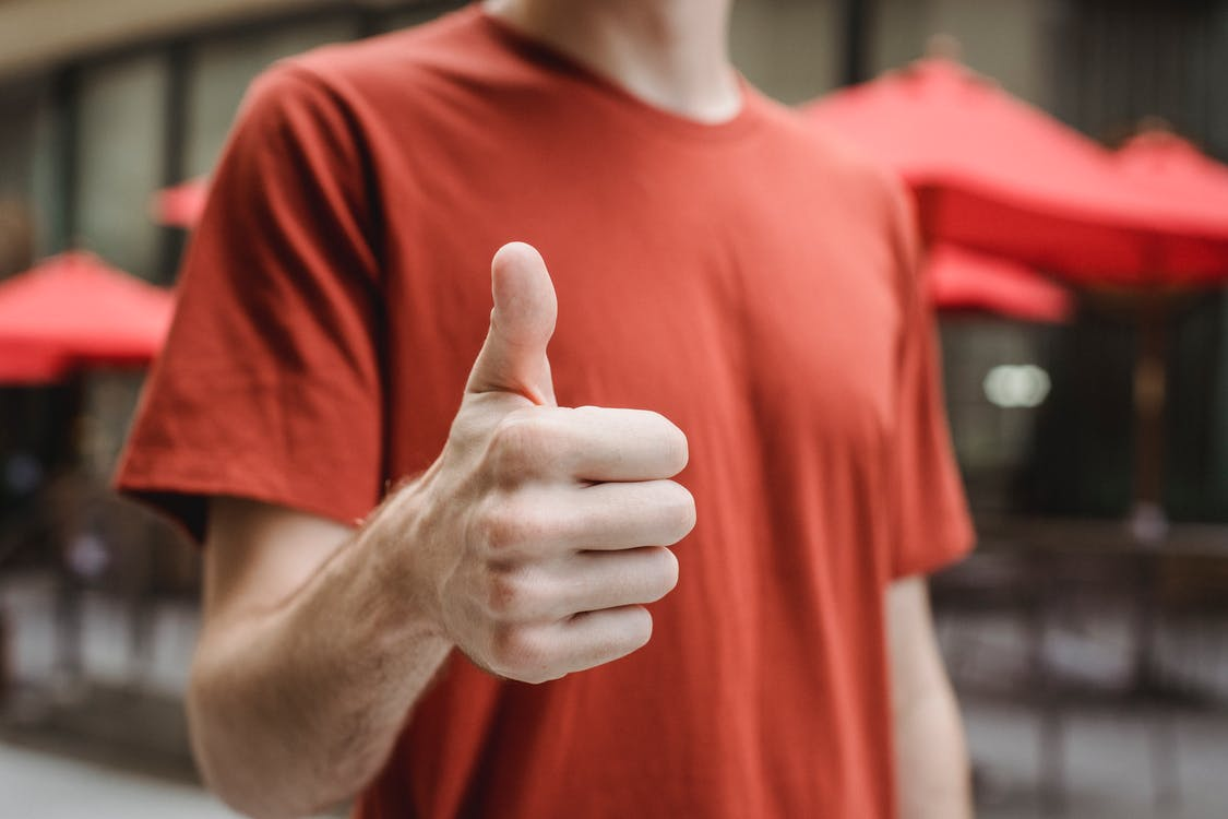 Crop anonymous young male in red t shirt showing thumb up gesture while standing on city street on sunny day
