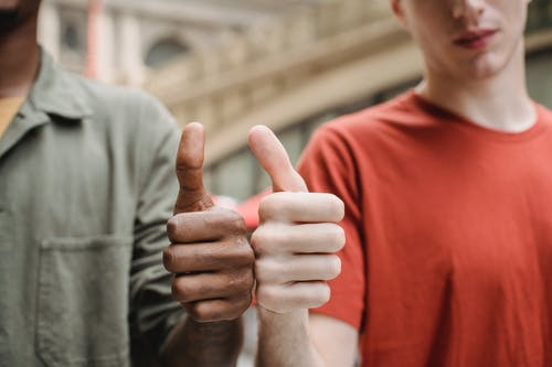Unrecognizable multiracial guys showing thumbs up gesture
