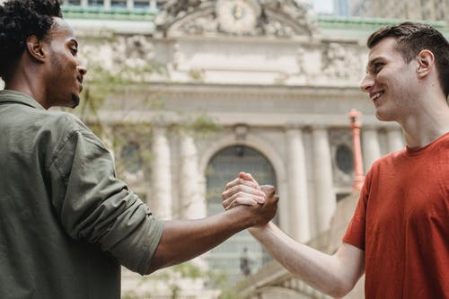 Side view of cheerful young multiracial male friends in trendy outfits smiling and looking at each other while shaking hands on city street after meeting