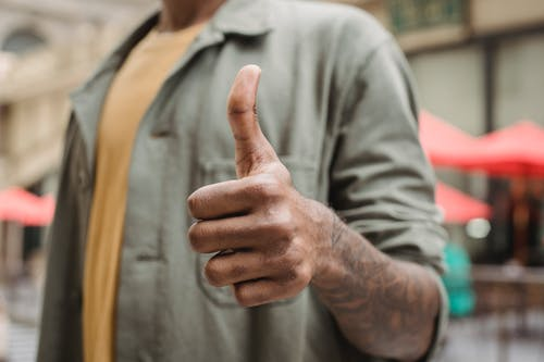 Crop faceless young black male in casual outfit standing on city street and showing thumb up gesture