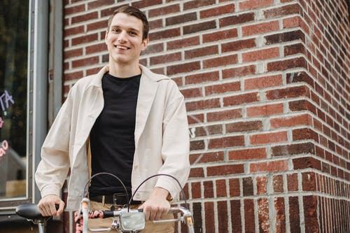 Low angle of cheerful young male millennial in stylish clothes smiling while standing on street with bicycle and looking at camera