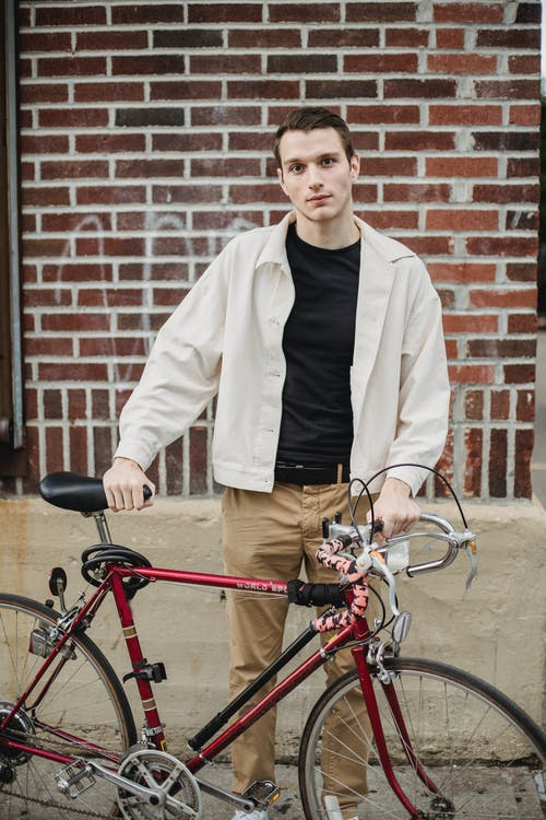 Serious young male millennial with bike standing on city street