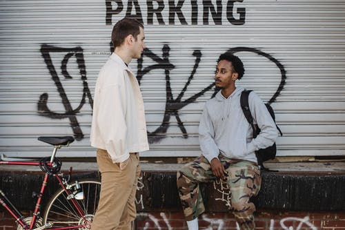 Serious young multiracial male friends spending time together on city street near aged building with graffiti after riding bicycle