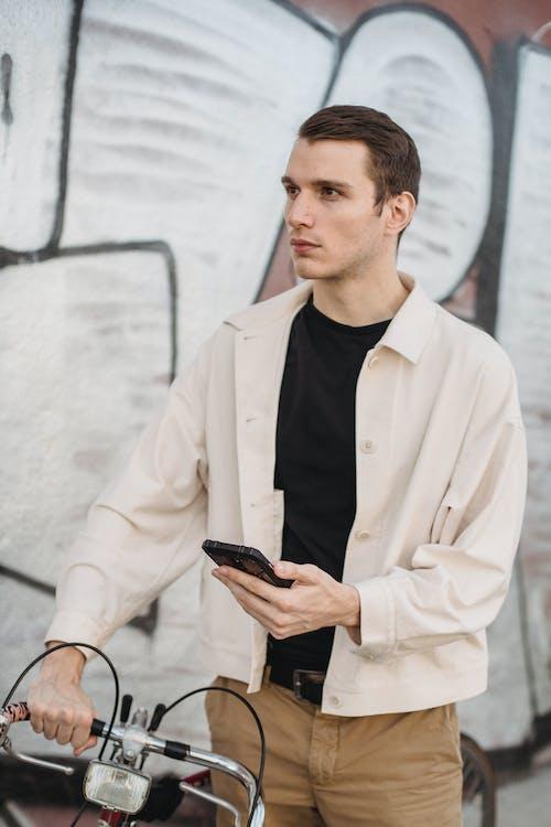 Serious young man using smartphone near graffiti wall