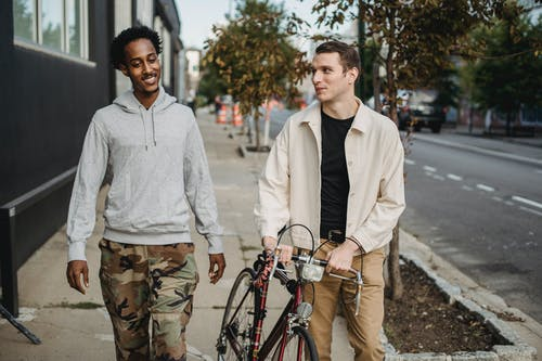 Happy young guy in casual clothes rolling bike while walking on city street with smiling African American male friend