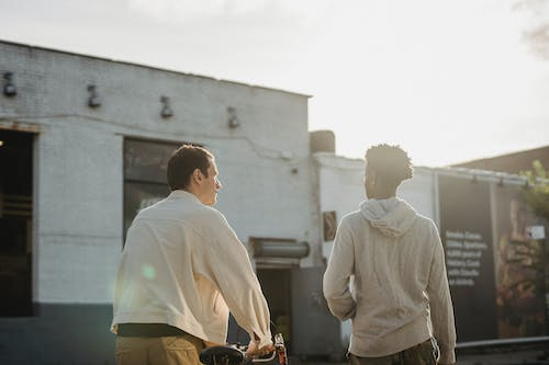 Back view of anonymous young multiracial male millennials in trendy outfits walking together on street and rolling bicycle near aged building in suburb area