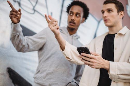 Pria Berkemeja Putih Memegang Smartphone Hitam