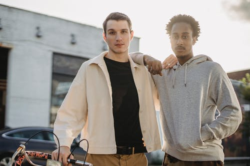 Confident young multiethnic male best friends in trendy clothes standing on city street at sunset and looking at camera