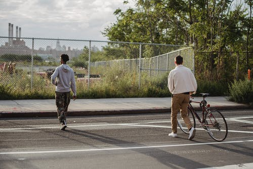 Back view of anonymous young male millennial in trendy outfit rolling bicycle while crossing asphalt road with African American friends in city outskirts