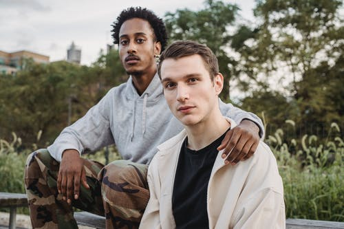 Focused young multiracial male best friends resting in city park