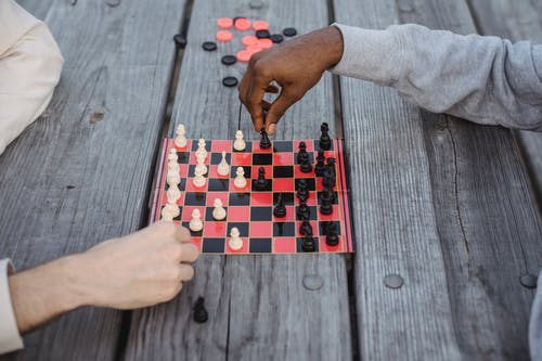 From above of crop anonymous multiethnic friends playing chess sitting at wooden table