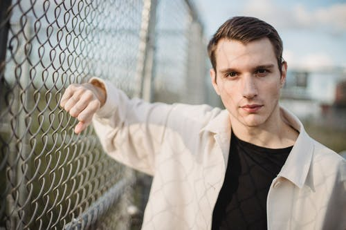 Young serious male in shadow wearing casual outfit leaning on metal net and looking at camera