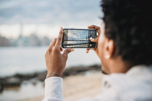 Back view of crop African American male taking picture on mobile phone of coastal city located on river bank