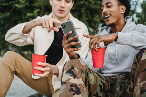 Multiethnic friends using smartphone together sitting with cups