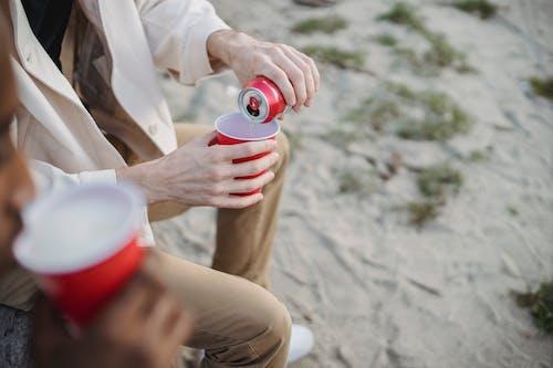 Persona In Camicia Bianca Abbottonata Che Tiene Tazza Di Plastica Rossa E Bianca