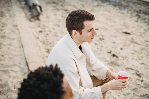 High angle of peaceful man with plastic cup sitting with African American friend on sandy  coast