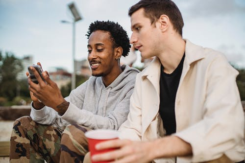 Cheerful black man showing video on mobile phone to friend
