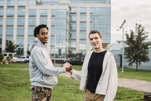 Young diverse male friends shaking hands while standing on lawn against modern building and looking at camera