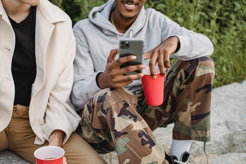Crop positive African American male browsing mobile phone while drinking beer from red cups with friend