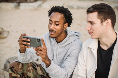 Attentive African American male sharing mobile phone with friend and watching video on sandy ground