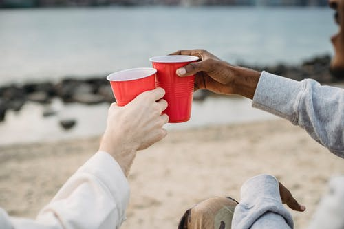 Diverse friends toasting with red cups on beach