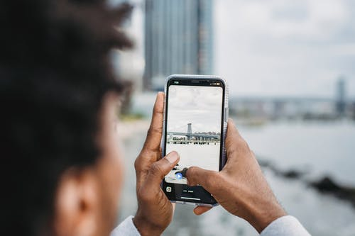 Black man taking photo of bridge over river