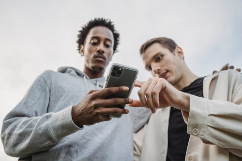 Multiethnic friends browsing smartphone together outside