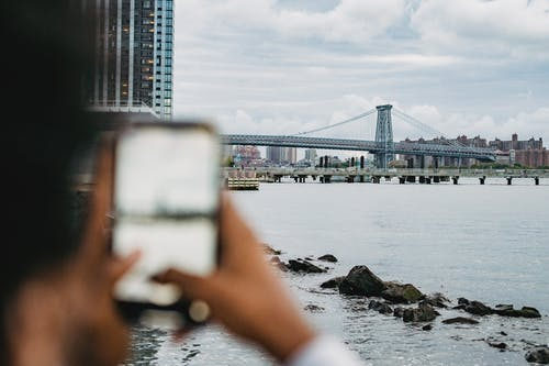 Crop anonymous African American male standing on embankment and taking picture of skyscrapers and bridge