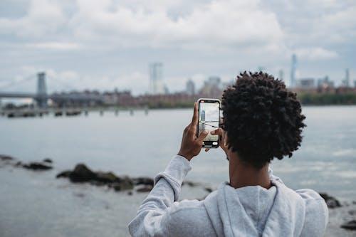 Black man taking photo of bridge on smartphone