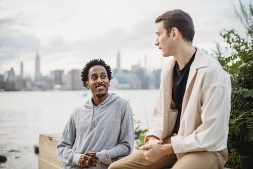 Positive African American male leaning on concrete border while having conversation with friend on city waterfront